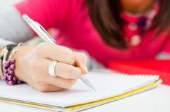 Κινηματογράφηση σε πρώτο πλάνο του γραψίματος χεριών κοριτσιών στοκ εικόνες