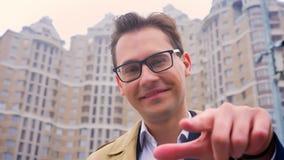 Κινηματογράφηση σε πρώτο πλάνο του ελκυστικού βέβαιου ατόμου που δείχνει στη κάμερα στο υπόβαθρο των υψηλών κτηρίων Μπορείτε να τ απόθεμα βίντεο