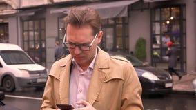 Κινηματογράφηση σε πρώτο πλάνο του ενήλικου καυκάσιου ατόμου που αναμένει για κάποιο που στέκεται στην οδό που ελέγχει το τηλέφων απόθεμα βίντεο