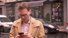 Κινηματογράφηση σε πρώτο πλάνο του ενήλικου καυκάσιου ατόμου στα γυαλιά που ελέγχει το τηλέφωνο που στέκεται στην οδό που αναμένε φιλμ μικρού μήκους