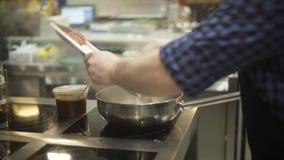 Κινηματογράφηση σε πρώτο πλάνο του επαγγελματικού τηγανίσματος αρχιμαγείρων στο τηγάνι στην κουζίνα r Ορεκτικός μαγειρεύοντας αρχ απόθεμα βίντεο
