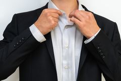 Κινηματογράφηση σε πρώτο πλάνο του επιχειρηματία στο επίσημο κοστούμι που διορθώνει ένα πουκάμισο στοκ φωτογραφία