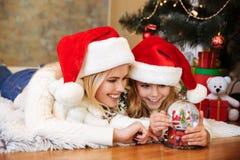 Κινηματογράφηση σε πρώτο πλάνο του ευτυχούς παιχνιδιού μικρών κοριτσιών με το παιχνίδι σφαιρών χιονιού ενώ λ Στοκ εικόνα με δικαίωμα ελεύθερης χρήσης