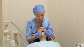 Κινηματογράφηση σε πρώτο πλάνο του ευτυχούς χαμογελώντας κοριτσιού στην οδοντιατρική στο γραφείο γιατρών ` s απόθεμα βίντεο