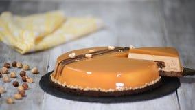 Κινηματογράφηση σε πρώτο πλάνο του εύγευστου κομματιού mousse του κέικ που ολοκληρώνεται με το λούστρο καθρεφτών καραμέλας Νόστιμ απόθεμα βίντεο