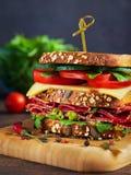 Κινηματογράφηση σε πρώτο πλάνο του εύγευστου σάντουιτς με το σαλάμι, το τυρί και τα φρέσκα λαχανικά στοκ φωτογραφία