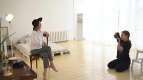 Κινηματογράφηση σε πρώτο πλάνο του θηλυκού φωτογράφου που παίρνει την εικόνα του όμορφου προτύπου στο επαγγελματικό στούντιο φωτο φιλμ μικρού μήκους
