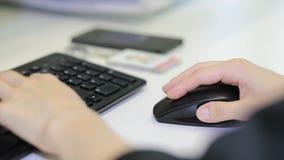 Κινηματογράφηση σε πρώτο πλάνο του θηλυκού χεριού στο μαύρο ποντίκι Χέρι γυναικών ` s που χρησιμοποιεί το ασύρματο ποντίκι στον ά Στοκ φωτογραφία με δικαίωμα ελεύθερης χρήσης