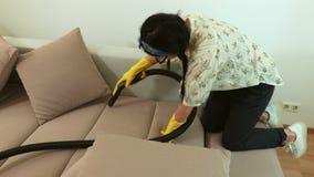 Κινηματογράφηση σε πρώτο πλάνο του καθαρίζοντας καναπέ γυναικών με την κίτρινη ηλεκτρική σκούπα απόθεμα βίντεο
