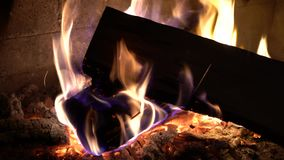 Κινηματογράφηση σε πρώτο πλάνο του καψίματος του ξύλου στην παραδοσιακή εστία τούβλου στο σκοτάδι φιλμ μικρού μήκους