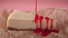 Κινηματογράφηση σε πρώτο πλάνο του κομματιού cheesecake που διακοσμείται από την κόκκινη μαρμελάδα σε ένα χαρτί συσκευασίας τροφί απόθεμα βίντεο