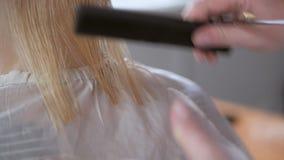 Κινηματογράφηση σε πρώτο πλάνο του κομμωτή που κάνει το κούρεμα στη γυναίκα με το ψαλίδι στο κομμωτήριο διαδικασία κουρέματος Λευ απόθεμα βίντεο