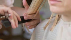 Κινηματογράφηση σε πρώτο πλάνο του κομμωτή που κάνει το κούρεμα στη γυναίκα με το ψαλίδι στο κομμωτήριο διαδικασία κουρέματος Λευ φιλμ μικρού μήκους