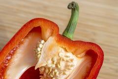 Κινηματογράφηση σε πρώτο πλάνο του κόκκινου πιπεριού κουδουνιών που τεμαχίζεται στο μισό, τους σπόρους και τη juicy σάρκα Στοκ φωτογραφία με δικαίωμα ελεύθερης χρήσης