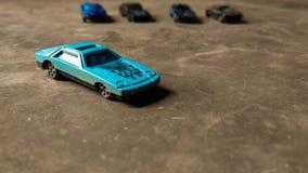 Κινηματογράφηση σε πρώτο πλάνο του μπλε αυτοκινήτου παιχνιδιών για τα παιδιά στο διαφορετικό υπόβαθρο με τα διάφορα αυτοκίνητα πα στοκ εικόνες