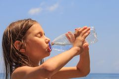 Κινηματογράφηση σε πρώτο πλάνο του νέου κοριτσιού που πίνει το φρέσκο κρύο νερό από το πλαστικό μπουκάλι κατανάλωσης μια καυτή θε στοκ φωτογραφίες