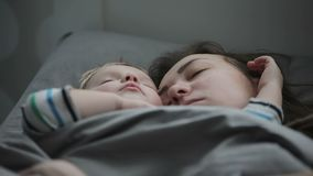 Κινηματογράφηση σε πρώτο πλάνο του νέου ύπνου μητέρων με το γιο μωρών στο κρεβάτι ? φιλμ μικρού μήκους