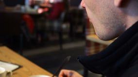 Κινηματογράφηση σε πρώτο πλάνο του νεαρού άνδρα που τρώει τη νόστιμα σούπα και το κουλούρι στον καφέ Θολωμένος καφές εσωτερικό 4k απόθεμα βίντεο