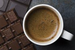 Κινηματογράφηση σε πρώτο πλάνο του νόστιμου καφέ με τα κομμάτια της σοκολάτας στον γκρίζο πίνακα στοκ εικόνες