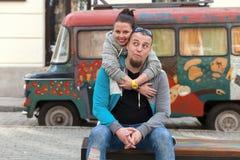 Κινηματογράφηση σε πρώτο πλάνο του οικογενειακού ζεύγους κοντά στο ζωηρόχρωμο παλαιό αυτοκίνητο ζωγραφικής ή το φορτηγό χίπηδων τ Στοκ εικόνες με δικαίωμα ελεύθερης χρήσης