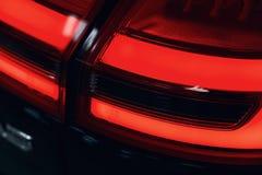 Κινηματογράφηση σε πρώτο πλάνο του οπίσθιου φωτός ενός σύγχρονου αυτοκινήτου Οδηγημένη οπτική στοκ εικόνα