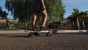 Κινηματογράφηση σε πρώτο πλάνο του ποδιού ενός σκέιτερ στην επιτροπή Γύροι Longboard στο δρόμο σε σε αργή κίνηση φιλμ μικρού μήκους