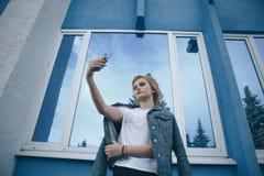 Κινηματογράφηση σε πρώτο πλάνο του πορτρέτου ύφους οδών μόδας του όμορφου κοριτσιού στην περιστασιακή εξάρτηση που περπατά γύρω α στοκ φωτογραφίες