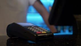Κινηματογράφηση σε πρώτο πλάνο του προσώπου που ψωνίζει και που πληρώνει χρησιμοποιώντας την τεχνολογία στο smartphone για την αν απόθεμα βίντεο