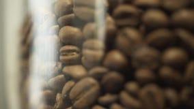 Κινηματογράφηση σε πρώτο πλάνο του συνόλου βάζων γυαλιού των φρέσκων καφετιών φασολιών καφέ που στέκονται στο ράφι ή τον πίνακα σ απόθεμα βίντεο