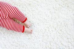 Κινηματογράφηση σε πρώτο πλάνο του σώματος και των ποδιών μωρών στο κόκκινο παντελόνι Άγιου Βασίλη στα Χριστούγεννα Στοκ Εικόνες