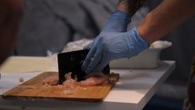 Κινηματογράφηση σε πρώτο πλάνο του τέμνοντος κρέατος αρχιμαγείρων χεριών απόθεμα βίντεο