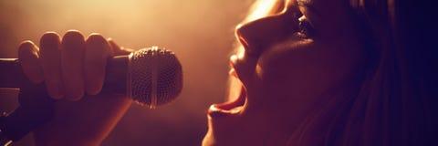 Κινηματογράφηση σε πρώτο πλάνο του τραγουδιού γυναικών στη συναυλία στοκ εικόνες
