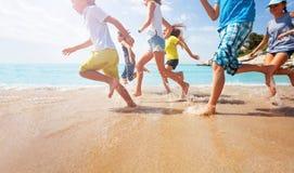 Κινηματογράφηση σε πρώτο πλάνο του τρεξίματος των ποδιών παιδιών στο ρηχό θαλάσσιο νερό Στοκ Εικόνες