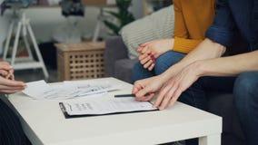 Κινηματογράφηση σε πρώτο πλάνο του τύπου που υπογράφει το σπίτι αγοράς συμβάσεων που παίρνει έπειτα το βασικό και χέρι τινάγματος απόθεμα βίντεο