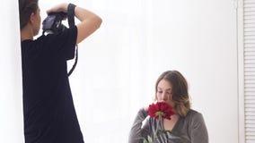 Κινηματογράφηση σε πρώτο πλάνο του φωτογράφου στο επαγγελματικό στούντιο που παίρνει τις εικόνες του προτύπου με το μεγάλο κόκκιν απόθεμα βίντεο