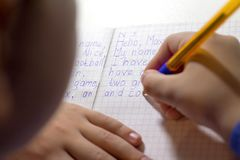 Κινηματογράφηση σε πρώτο πλάνο του χεριού αγοριών με το μολύβι που γράφει τις αγγλικές λέξεις με το χέρι σε παραδοσιακό άσπρο χαρ Στοκ εικόνες με δικαίωμα ελεύθερης χρήσης