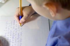Κινηματογράφηση σε πρώτο πλάνο του χεριού αγοριών με το μολύβι που γράφει τις αγγλικές λέξεις με το χέρι σε παραδοσιακό άσπρο χαρ Στοκ φωτογραφία με δικαίωμα ελεύθερης χρήσης