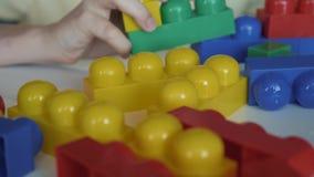 Κινηματογράφηση σε πρώτο πλάνο του χεριού αγοριών ` s που συλλέγει την αναπτυσσόμενη συνεδρίαση lego σχεδιαστών στον άσπρο πίνακα φιλμ μικρού μήκους
