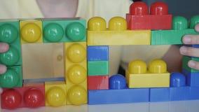 Κινηματογράφηση σε πρώτο πλάνο του χεριού αγοριών ` s που συλλέγει την αναπτυσσόμενη συνεδρίαση lego σχεδιαστών στον άσπρο πίνακα απόθεμα βίντεο