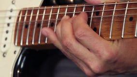 Κινηματογράφηση σε πρώτο πλάνο του χεριού ενός κιθαρίστα στο λαιμό της κιθάρας που παίζει επιδεικνύοντας πώς να κάνει σωστά την κ απόθεμα βίντεο