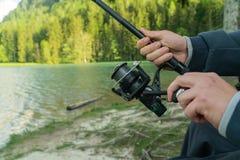 Κινηματογράφηση σε πρώτο πλάνο του χεριού ψαράδων s με την περιστροφή - εποχή θερινής αλιείας στοκ φωτογραφίες
