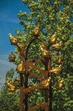 Κινηματογράφηση σε πρώτο πλάνο του χρυσού μνημείου πουλιών μετάλλων με το φυλλώδες δέντρο σε μια ηλιόλουστη ημέρα σε Weesp Στοκ φωτογραφία με δικαίωμα ελεύθερης χρήσης