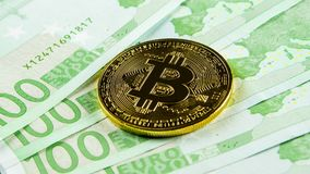 Κινηματογράφηση σε πρώτο πλάνο του χρυσού νομίσματος bitcoin στο ευρο- υπόβαθρο τραπεζογραμματίων Στοκ Εικόνα