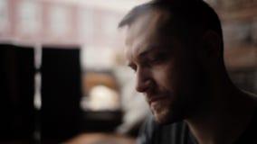 Κινηματογράφηση σε πρώτο πλάνο του όμορφου ατόμου με τη συνεδρίαση σκληρών τριχών δίπλα σε ένα παράθυρο στον καφέ απόθεμα βίντεο