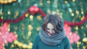 Κινηματογράφηση σε πρώτο πλάνο του όμορφου ερχομού κοριτσιών brunette χαμόγελου μέχρι τη κάμερα κοντά στο χριστουγεννιάτικο δέντρ φιλμ μικρού μήκους