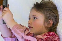Κινηματογράφηση σε πρώτο πλάνο του όμορφου μικρού κοριτσιού στο σχεδιάγραμμα που εξετάζει την τηλεφωνική οθόνη στοκ φωτογραφίες