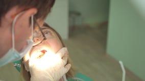 Κινηματογράφηση σε πρώτο πλάνο του όμορφου προσώπου γυναικών με τον οδοντίατρο στην κλινική με τον ειδικό φωτισμό και τον οδοντικ απόθεμα βίντεο