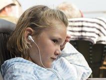 Κινηματογράφηση σε πρώτο πλάνο του όμορφου χαμογελώντας μικρού κοριτσιού στο σχεδιάγραμμα που ακούει τη μουσική στοκ εικόνα με δικαίωμα ελεύθερης χρήσης