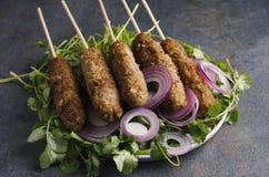 Κινηματογράφηση σε πρώτο πλάνο του kebab με τα καρυκεύματα, δαχτυλίδια κρεμμυδιών στο σκοτεινό αγροτικό πίνακα κουζινών στοκ εικόνα