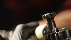Κινηματογράφηση σε πρώτο πλάνο του tatooer στα μαύρα γάντια που κάνουν το tatoo φιλμ μικρού μήκους